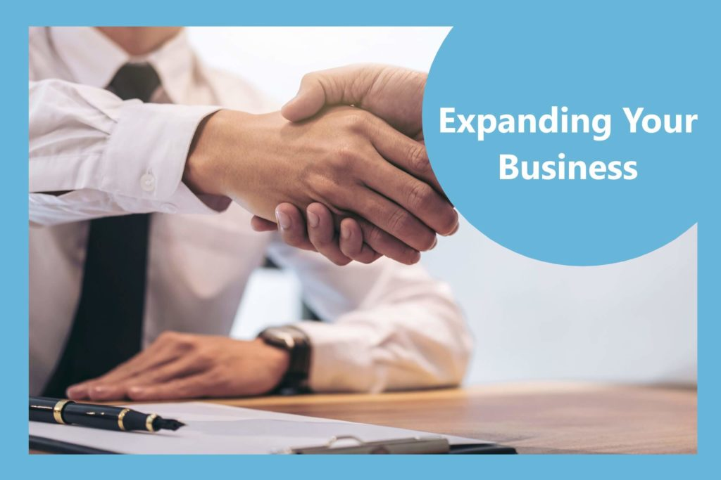 a bank manager accepting a business loan and shaking the clients hand
